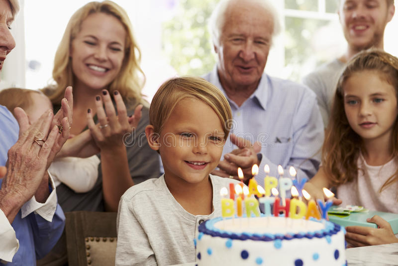 O menino funde para fora velas do bolo de aniversário no partido da família imagem de stock