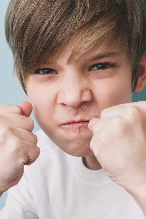O menino grita e ameaça na brincadeira com seus punhos na posição de combate fotos de stock royalty free