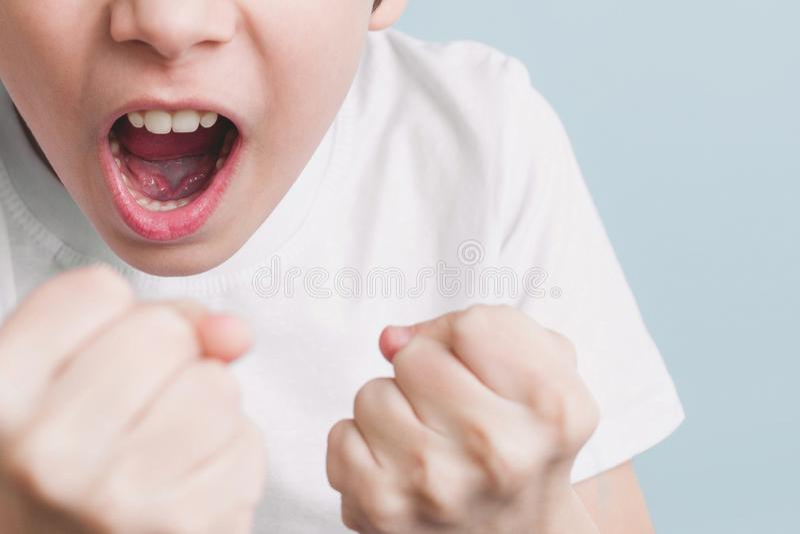 O menino grita e ameaça na brincadeira com seus punhos na posição de combate imagem de stock