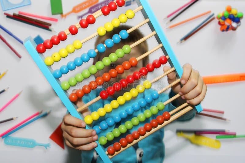 O menino guarda o ábaco grande em suas mãos O menino ama a matemática imagem de stock