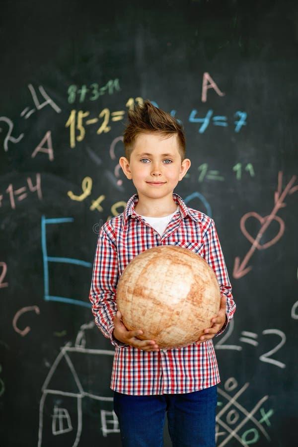 O menino guarda o globo perto da administração da escola fotos de stock
