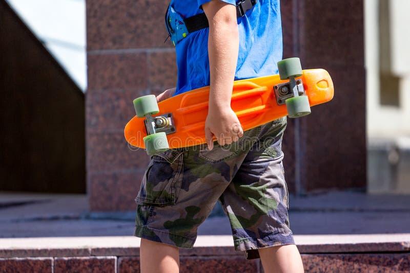 O menino guarda o patim em suas mãos O menino está indo rolar no skateboarding_ foto de stock royalty free