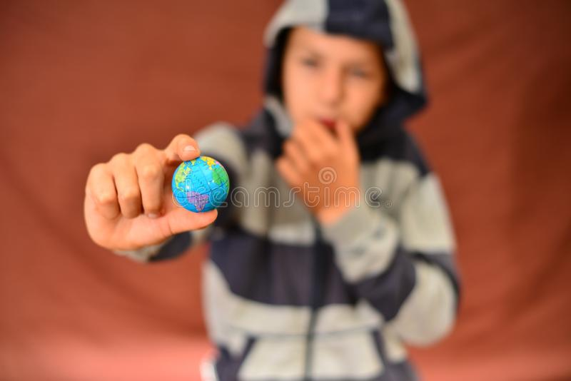 O menino guarda a terra do planeta em suas mãos, em um fundo vermelho fotografia de stock royalty free
