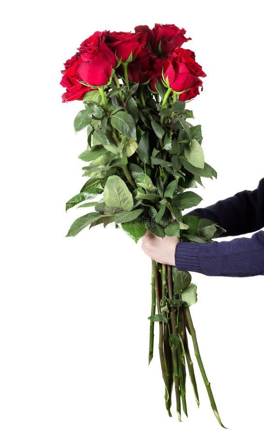O menino guarda um grande ramalhete de rosas vermelhas com hastes altas e o verde sae em suas mãos Flores para o mum Conceito do  fotografia de stock