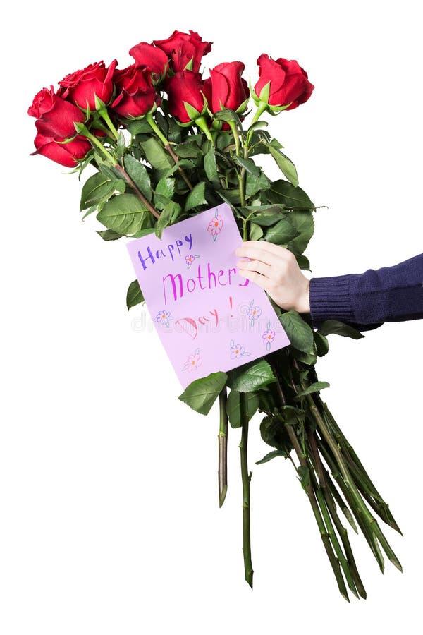 O menino guarda um grande ramalhete de rosas vermelhas e do cartão feito a mão para sua mãe em suas mãos Flores e presente para a fotos de stock royalty free
