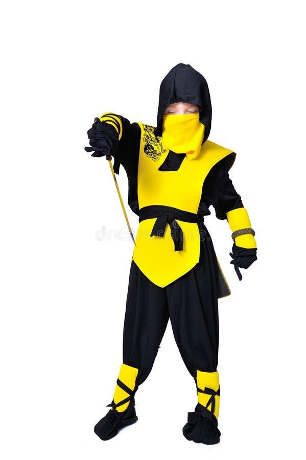 O menino idoso de sete-anos no terno preto e amarelo do ninja com ho imagens de stock