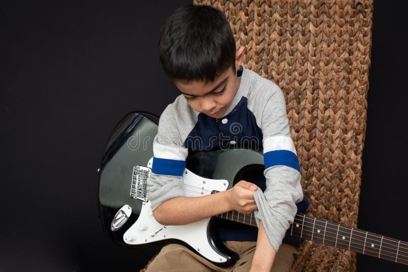 O menino indiano britânico da criança de 8 anos pratica a guitarra elétrica em casa imagens de stock