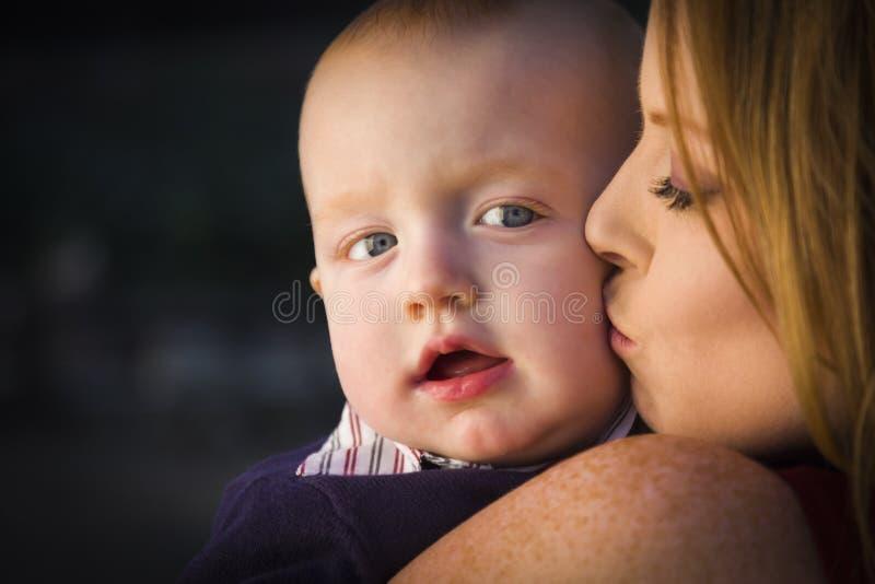 O menino infantil principal vermelho adorável é beijado por sua mãe fotos de stock