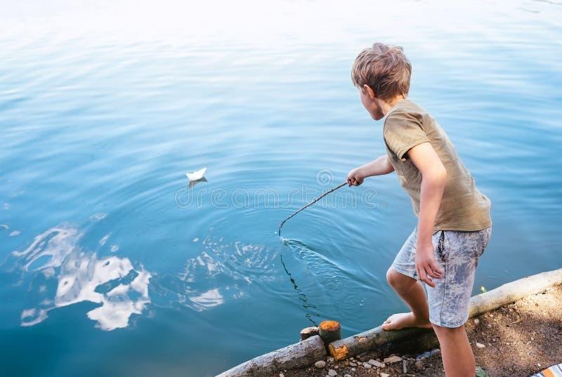 O menino joga com barco de papel e lança-o no lago fotografia de stock royalty free