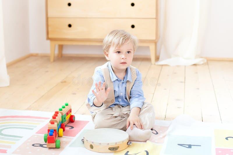 O menino joga com um cilindro de madeira musical e um trem Brinquedos de madeira educacionais para a criança Retrato de um menino imagem de stock