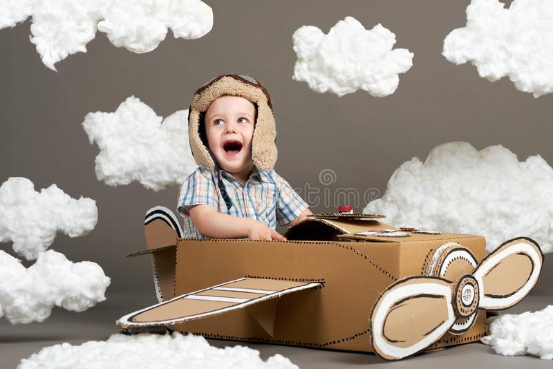 O menino joga em um avião feito da caixa de cartão e dos sonhos de transformar-se um piloto, nuvens do algodão em um fundo cinzen fotografia de stock