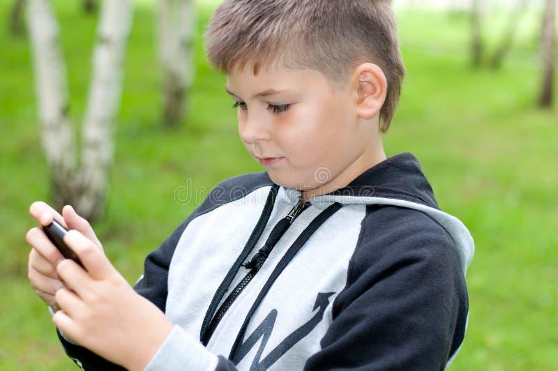 o menino joga em um telefone celular em um parque imagens de stock royalty free