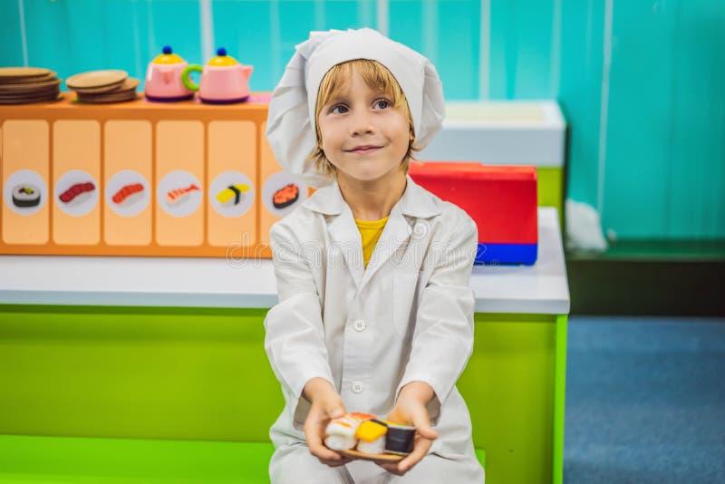 O menino joga o jogo como se era um cozinheiro em uma cozinha das crian?as foto de stock