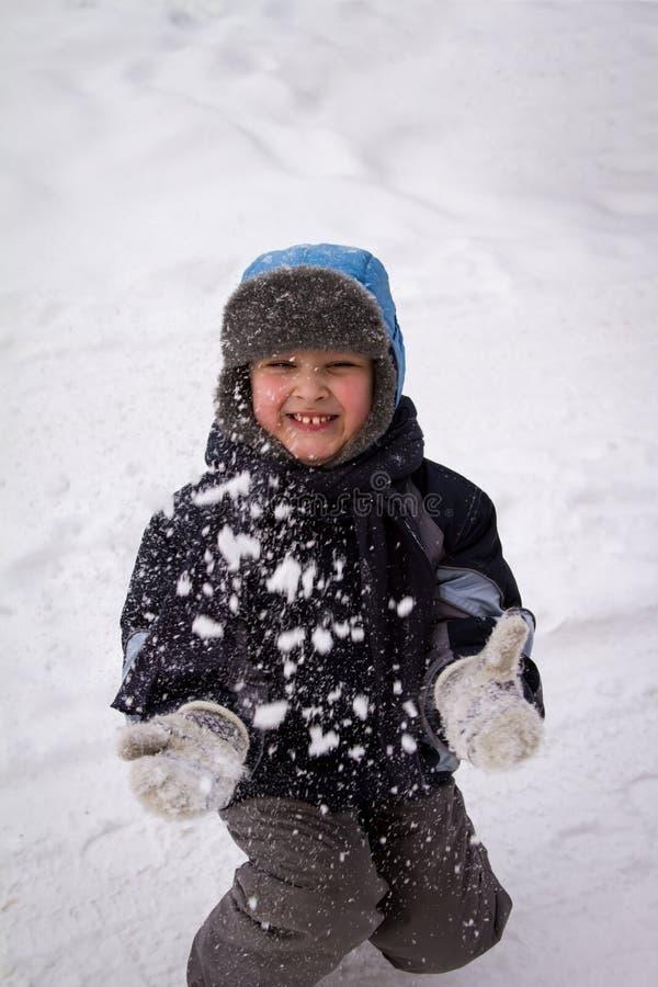 O menino joga a neve na parte superior fotos de stock royalty free