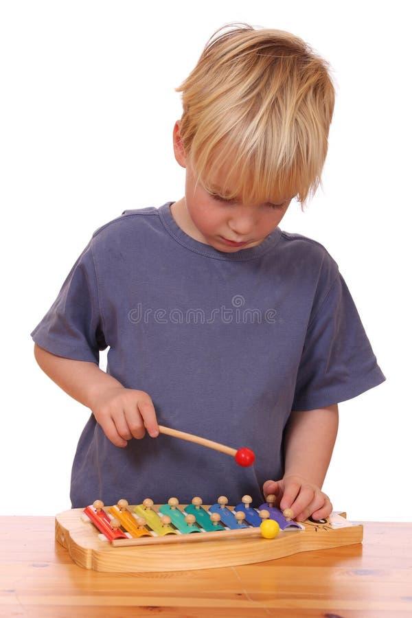 O menino joga o xylophone fotografia de stock royalty free