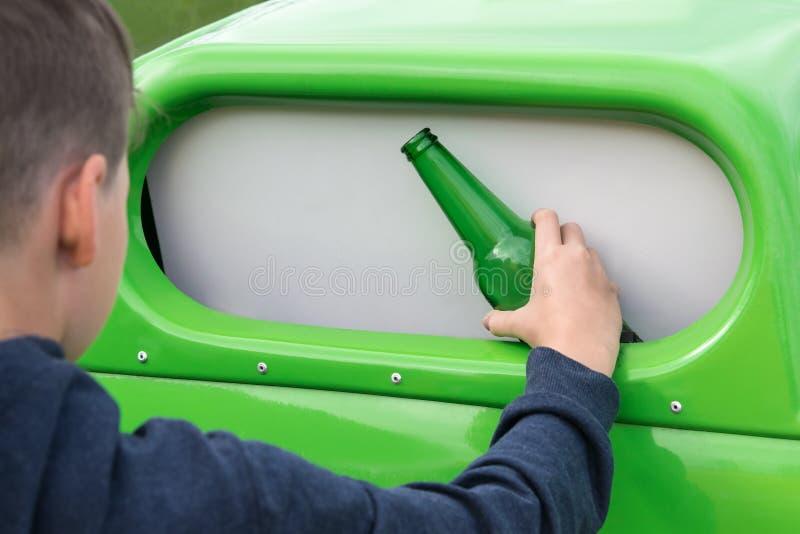 O menino joga para fora uma garrafa em um recipiente verde projetado para o desperdício de vidro fotografia de stock royalty free