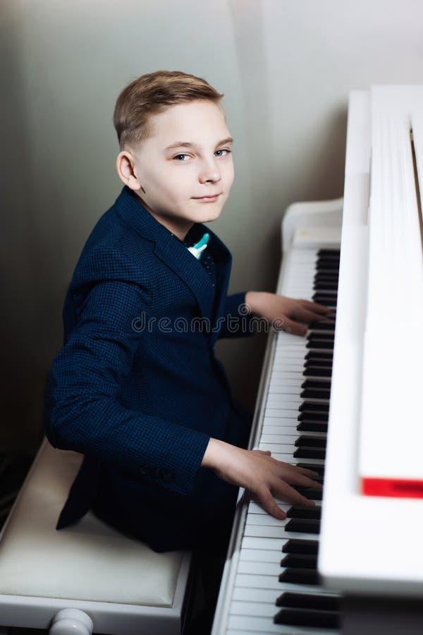 O menino joga o piano A criança à moda aprende jogar um instrumento musical foto de stock royalty free