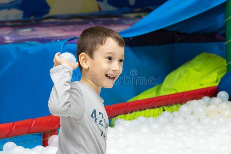 O menino joga uma bola plástica em uma associação seca de um centro de entretenimento das crianças Cheboksary, Rússia, 02/12/2018 foto de stock royalty free