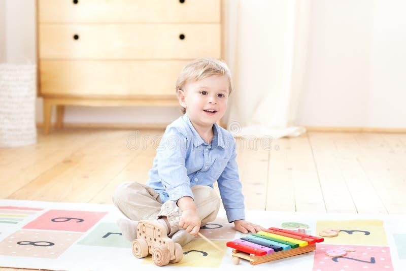 O menino joga o xilofone em casa Menino positivo de sorriso bonito que joga com um xilofone do instrumento musical do brinquedo n fotos de stock royalty free