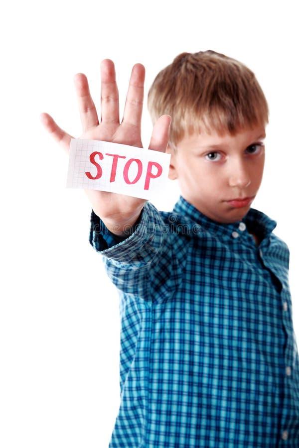 O menino louro bonito em uma camisa azul mostra uma parada da mensagem que olha triste imagens de stock royalty free