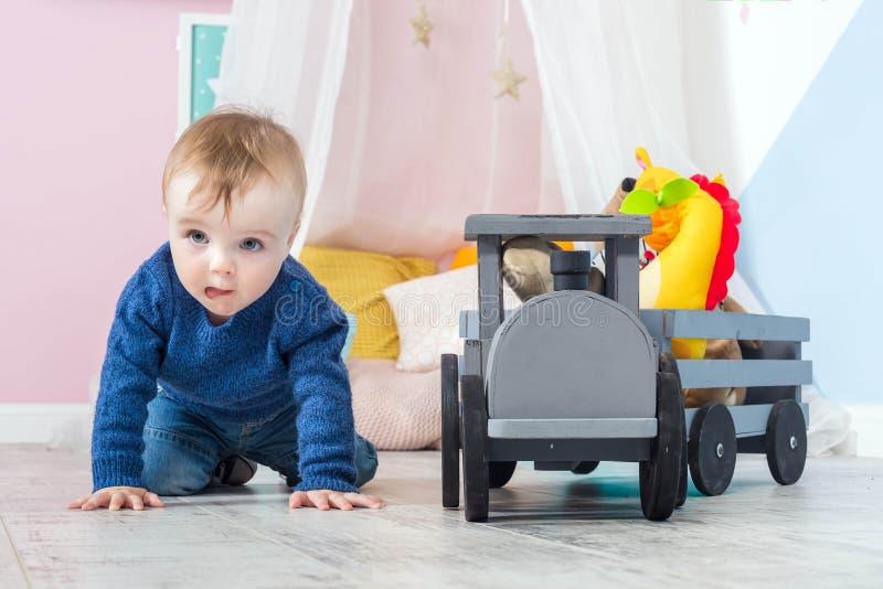 O menino louro em uma camiseta azul rasteja em um assoalho de madeira Beb? de um ano que joga com brinquedos de madeira trem feit imagem de stock royalty free