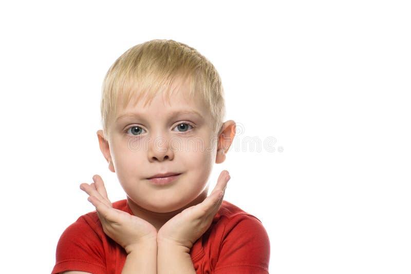 O menino louro pensativo em um t-shirt vermelho dobrou suas mãos em seu queixo Isolado em um fundo branco imagem de stock