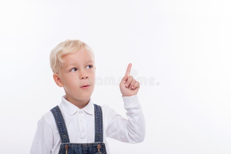 O menino louro pequeno alegre tem uma grande ideia fotografia de stock