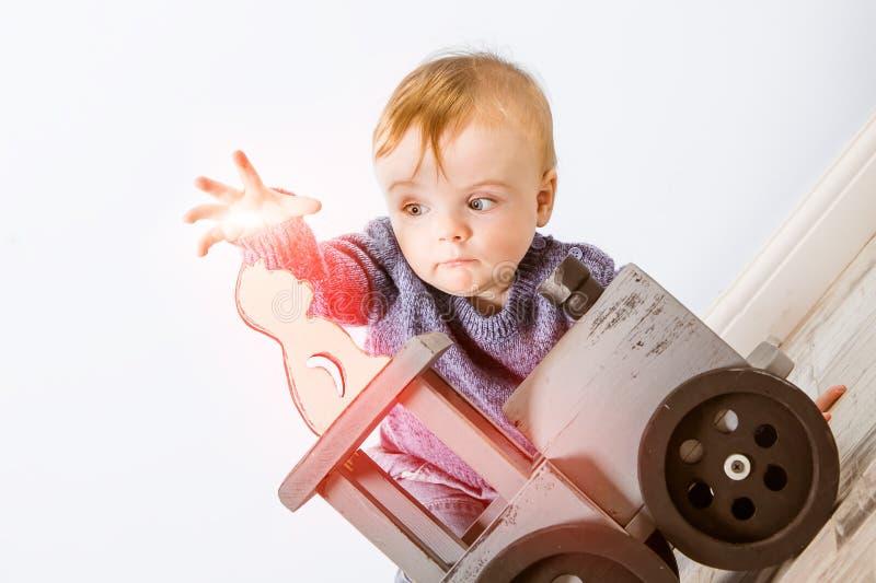 O menino louro pequeno feliz joga o feiticeiro e tenta-o reviver um gato de madeira Senta-se no assoalho na perspectiva de uma lu fotos de stock