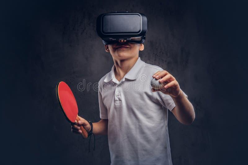 O menino louro vestiu-se em um t-shirt branco que joga o tênis de mesa com vidros de uma realidade virtual Isolado na obscuridade foto de stock