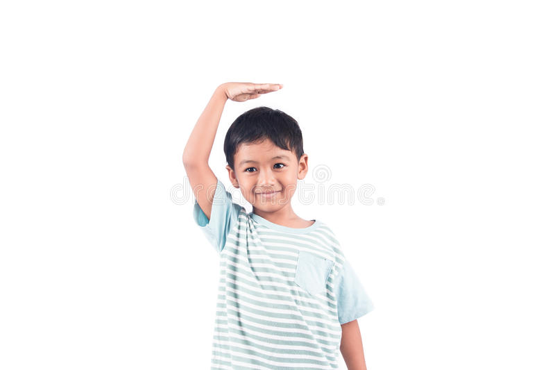 o menino mede sua altura com sua mão na cabeça foto de stock