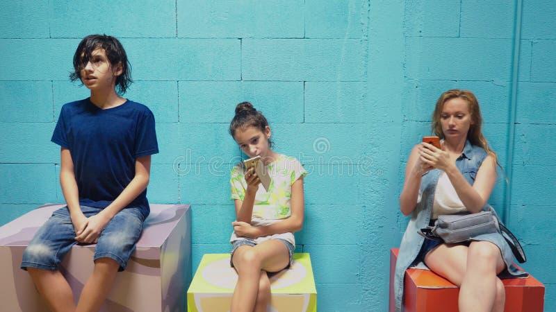 O menino, a menina e a mulher usam seus telefones celulares ao sentar-se contra a parede azul fotos de stock
