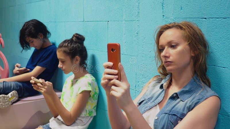 O menino, a menina e a mulher usam seus telefones celulares ao sentar-se contra a parede azul fotografia de stock