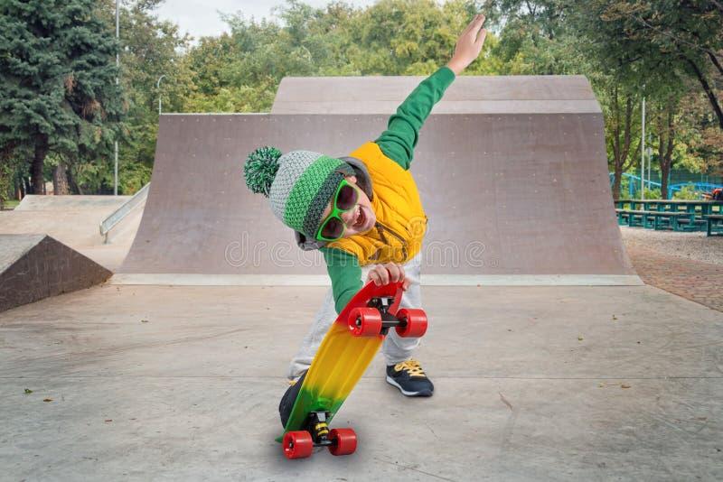O menino monta seu skate no parque do patim Esportes extremos fotografia de stock