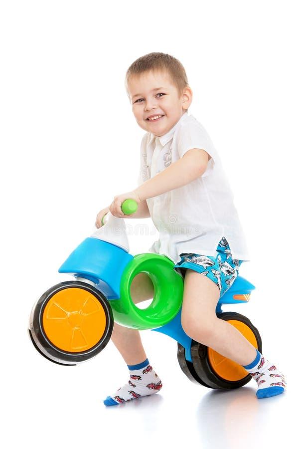 O menino monta uma bicicleta imagem de stock