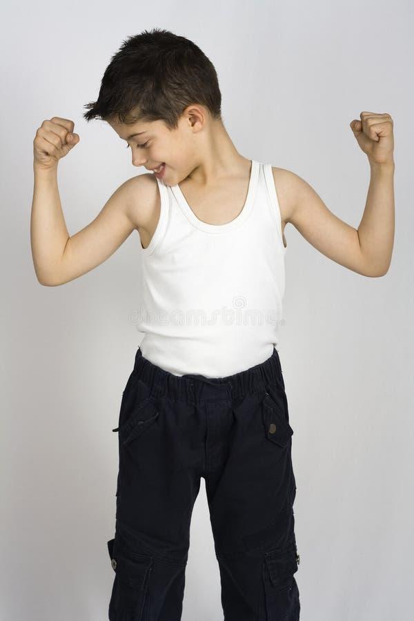 O menino mostra seus músculos imagem de stock royalty free