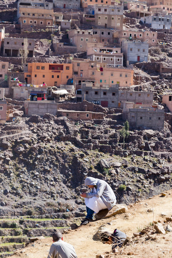 O menino muçulmano do berber novo comunica-se no assento móvel no mountai fotos de stock