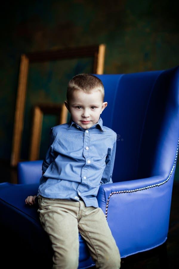 O menino na camisa e no veludo de algodão azuis arfa fotografia de stock royalty free