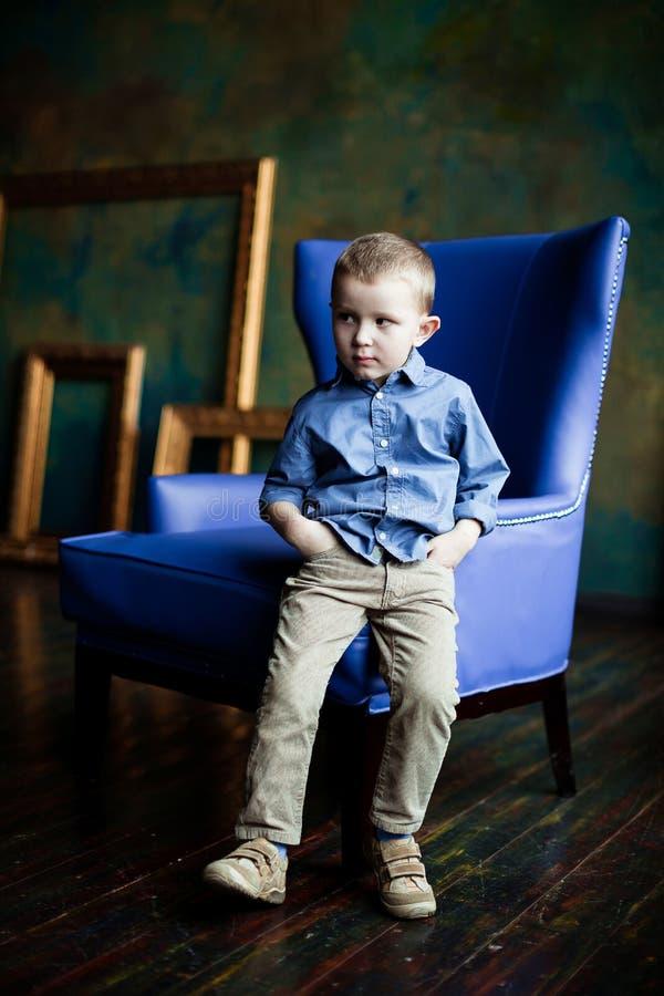 O menino na camisa e no veludo de algodão azuis arfa imagem de stock