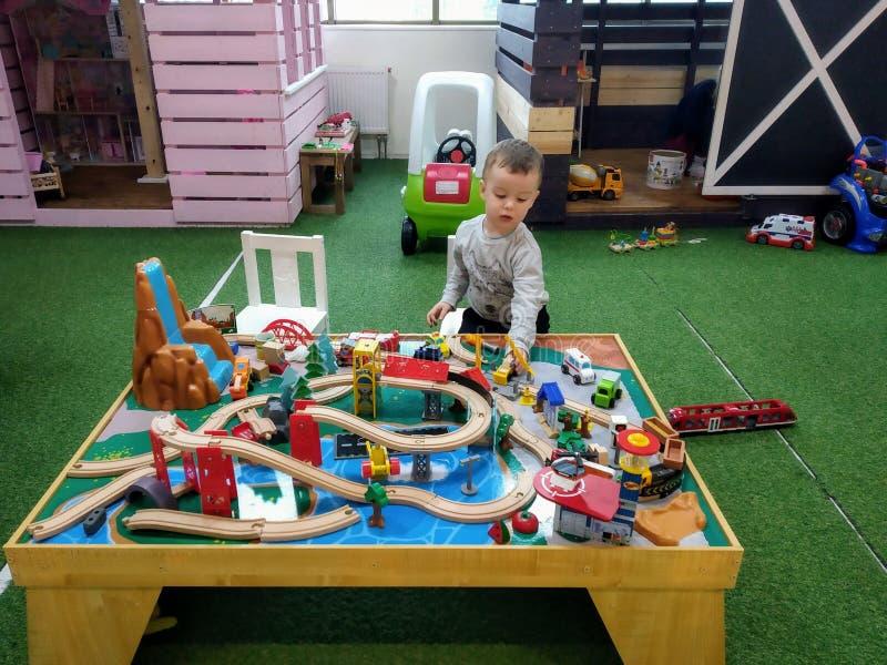 O menino na idade de 3 anos de jogos com a estrada de ferro das crianças de madeira em um canto no centro de entretenimento, a pa imagens de stock royalty free