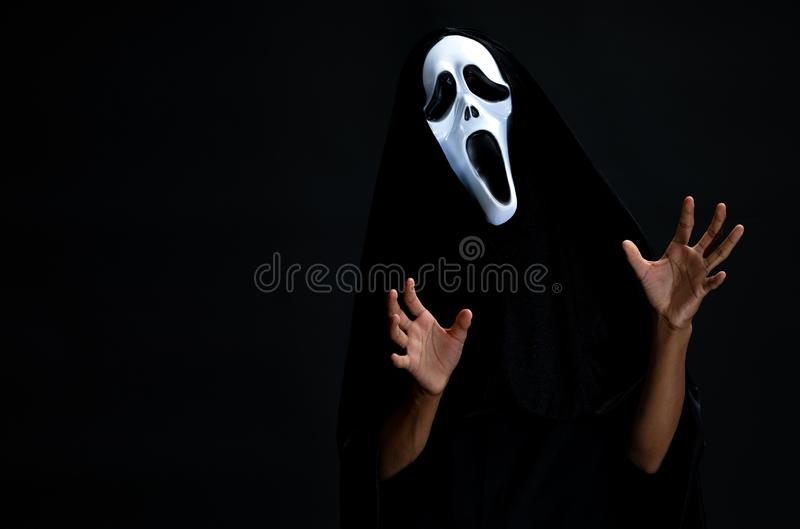 O menino na tampa preta com a máscara branca do fantasma cosplay à C.A. do diabo fotografia de stock