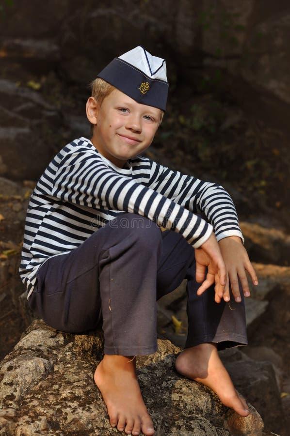 O menino na veste e no tampão marinho fotografia de stock royalty free