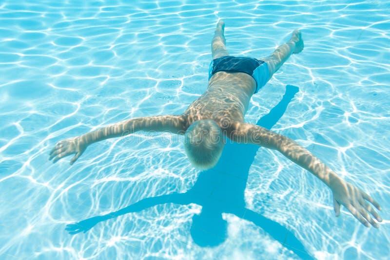 O menino nada sob a cara da água para baixo imagens de stock royalty free