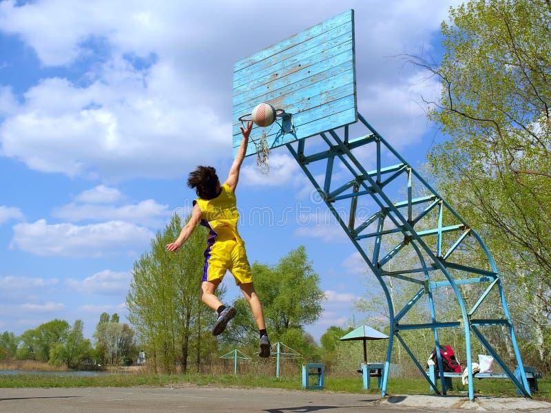 O menino no amarelo joga o basquetebol imagem de stock