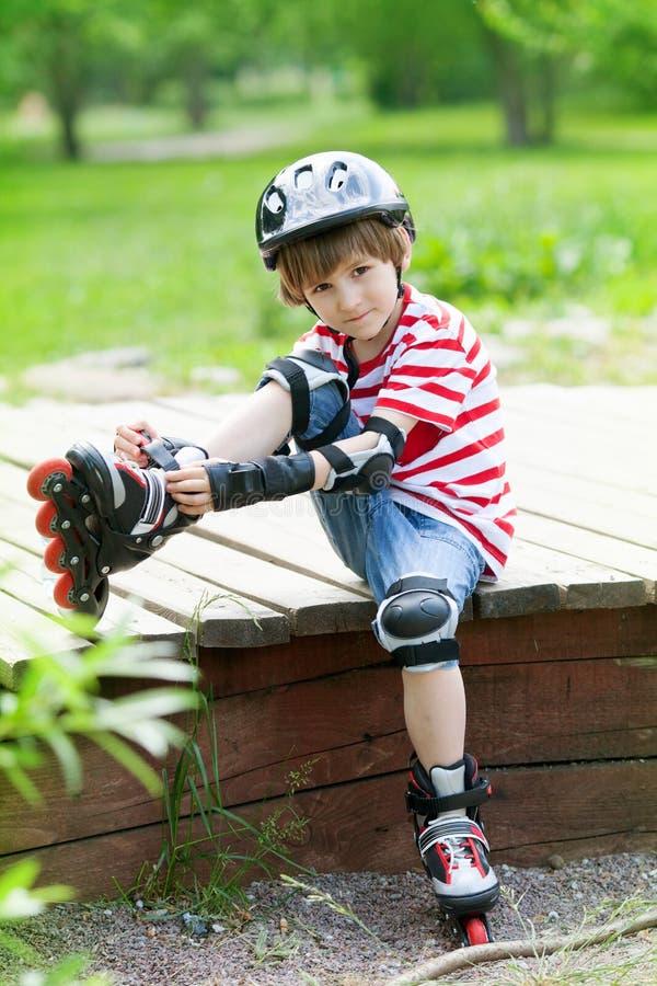 O menino no capacete pôs sobre patins de rolo imagens de stock
