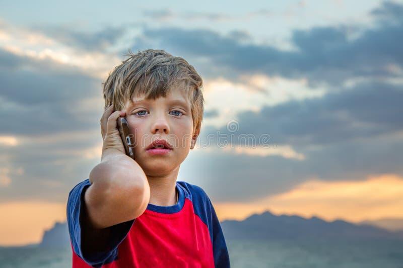 O menino no t-shirt vermelho está sentando-se fora e falando em seu telefone celular, olha virado ou assustado Um adolescente usa foto de stock