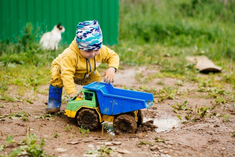 O menino no terno amarelo que joga com um carro do brinquedo na sujeira imagem de stock