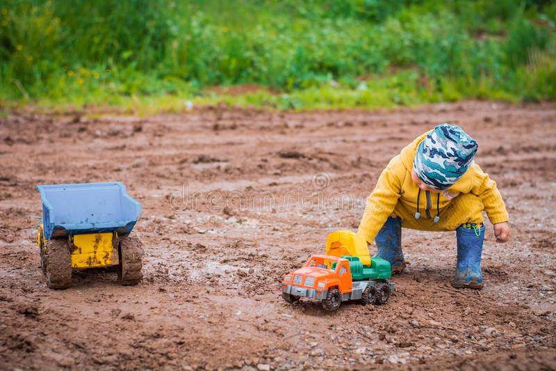 O menino no terno amarelo que joga com um carro do brinquedo na sujeira fotografia de stock