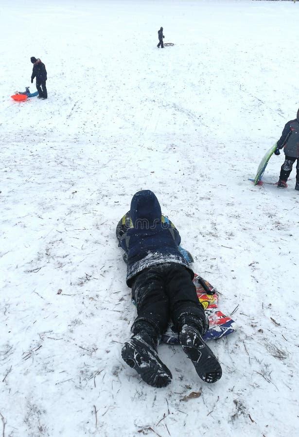 O menino no trenó espera sua volta ao trenó abaixo de um monte nevado imagens de stock royalty free
