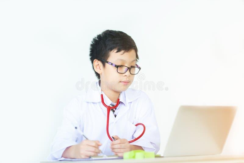 O menino no uniforme do médico usando uma pena na mesa, asiático novo finge a fotos de stock