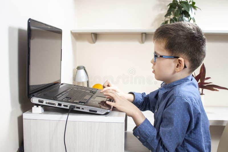 O menino nos vidros e em uma camisa azul está sentando-se em uma mesa na frente de um portátil e está jogando-se um jogo de compu imagem de stock